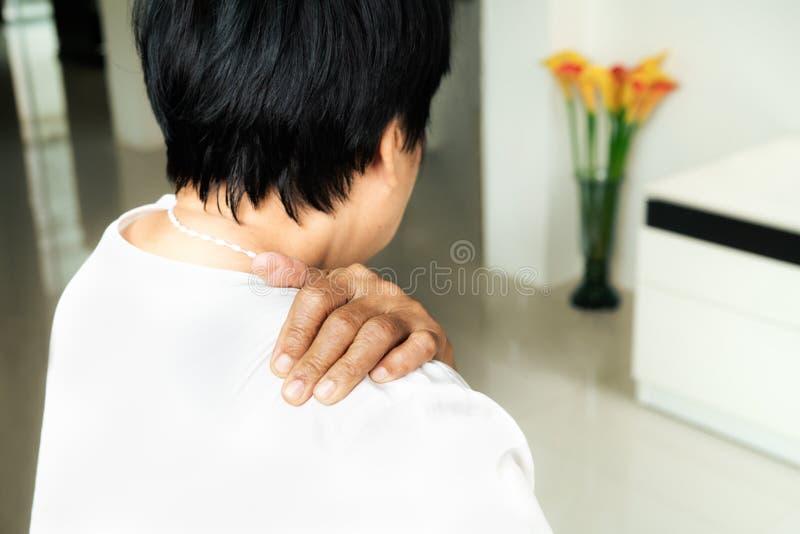 Il collo e la spalla fanno soffrire, donna anziana che soffrono dal collo e ferita sulla spalla, concetto di problema sanitario immagine stock