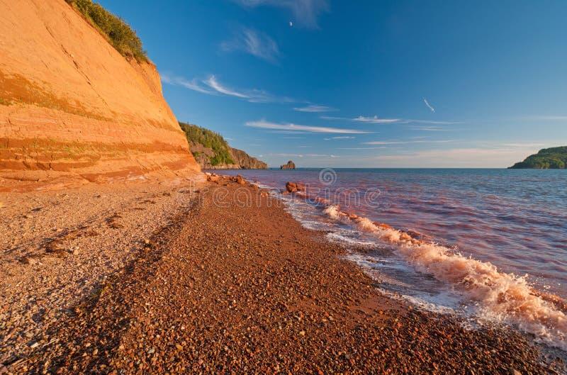 Il colore rosso fluttua su una spiaggia dell'arenaria rossa immagini stock libere da diritti
