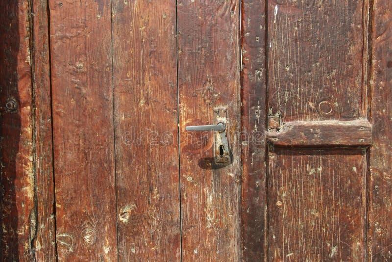 Il colore rosso scuro della vecchia porta di legno ed il vecchio ferro chiudono il frammento a chiave immagine stock libera da diritti