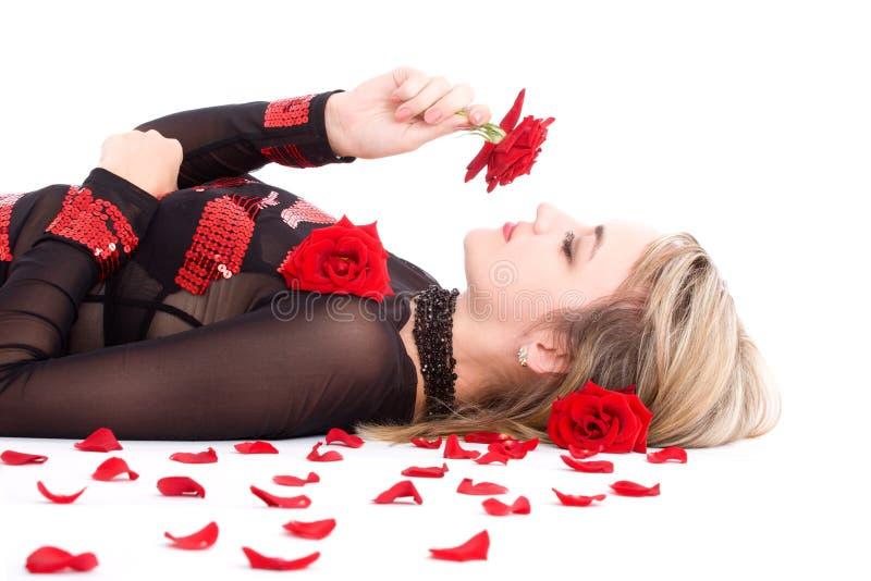 Il colore rosso sentente l'odore della giovane ragazza bionda è aumentato fotografia stock libera da diritti