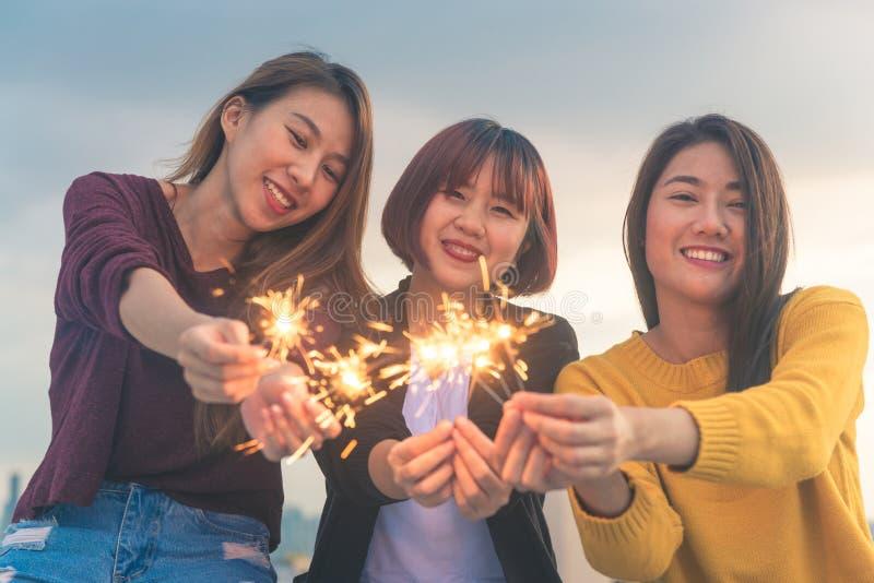 Il colpo all'aperto dei giovani al tetto fa festa Il gruppo felice di ragazze dell'Asia gode e gioca della stella filante al part immagine stock