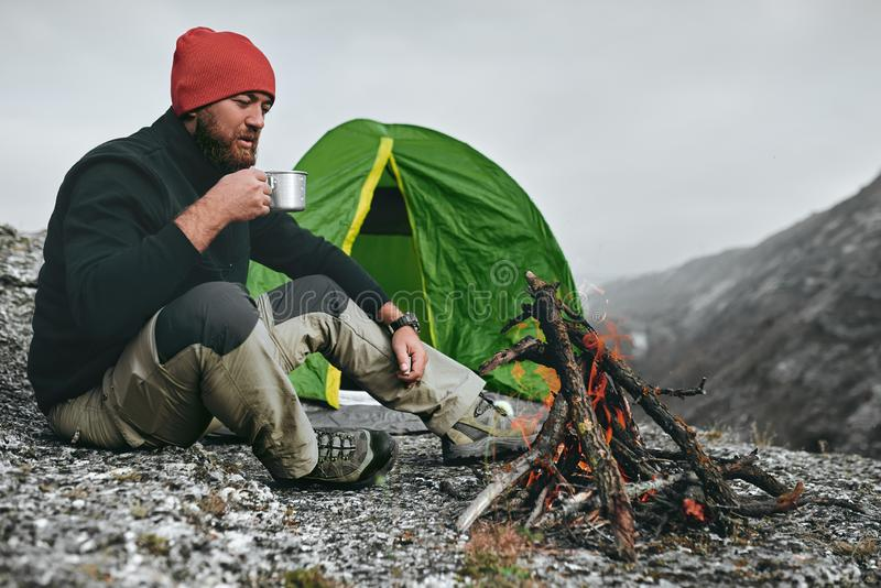 Il colpo all'aperto dei giovani ha impanato la bevanda calda bevente maschio in montagne Uomo del viaggiatore in cappello rosso,  immagine stock libera da diritti