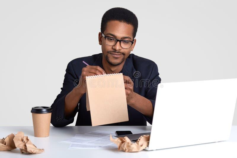 Il colpo del giornalista serio dell'uomo di colore lavora al nuovo articolo della creazione, annota le idee in blocco note a spir fotografia stock libera da diritti