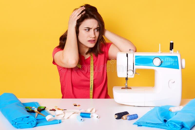 Il colpo dell'interno della cucitrice che cuce nello studio, tiene le mani sull'avuto su, ha rotto la macchina per cucire, maglie immagine stock