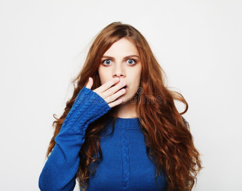 Il colpo dell'interno della donna bionda colpita stupefatta tiene la bocca ampiamente aperta, esamina la macchina fotografica, in immagine stock libera da diritti