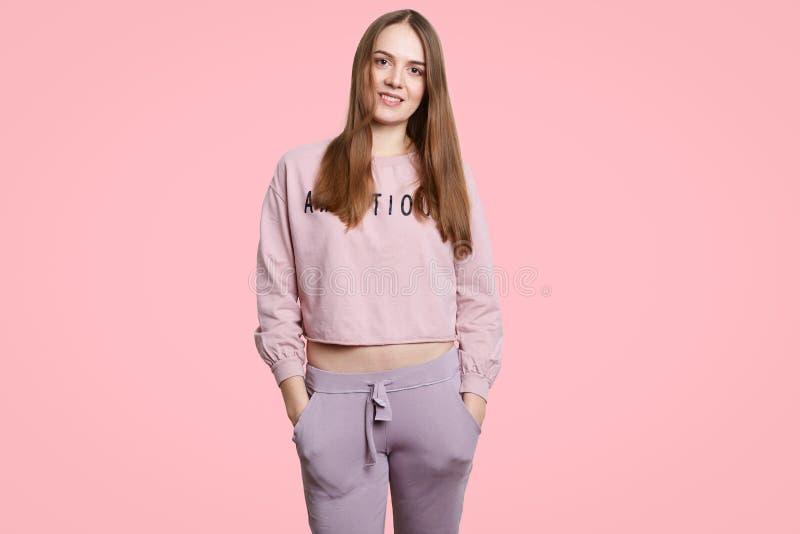 Il colpo dell'interno della donna felice di misura porta gli abiti sportivi casuali, tiene le mani in tasche, sta da solo contro  fotografia stock