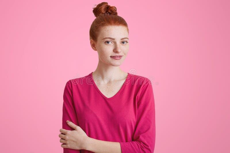 Il colpo dell'interno di bella femmina dai capelli rossi vestita casaully, ha nodo dei capelli, esamina felicemente la macchina f fotografia stock libera da diritti