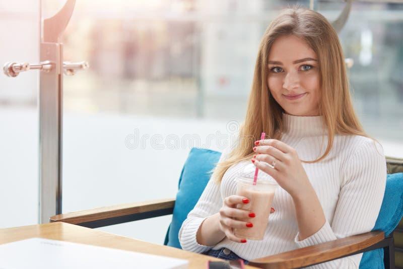 Il colpo dell'interno di bella giovane femmina sveglia sorridente ritiene rilassato mentre si siede sul sofà blu comodo in caffè, immagini stock