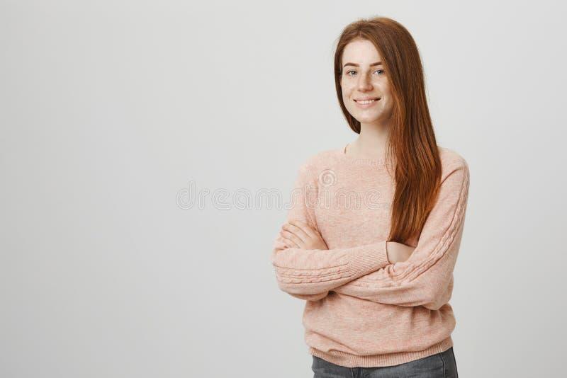 Il colpo dell'interno di giovane ragazza europea attraente dello zenzero con il sorriso timido che sta con attraversato consegna  immagine stock