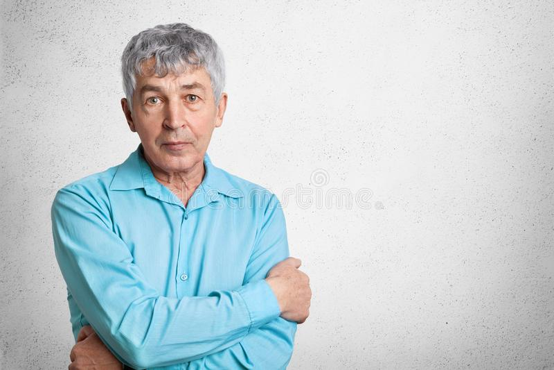 Il colpo dell'interno dell'uomo maturo sicuro in camicia convenzionale, tiene le mani attraversate, guarda direttamente nella mac immagine stock