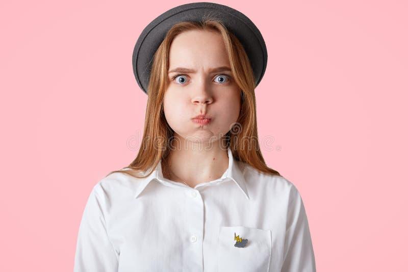 Il colpo della femmina osservata blu infastidita con l'aspetto piacevole, guance dei colpi, indossa black hat elegante e la camic fotografie stock
