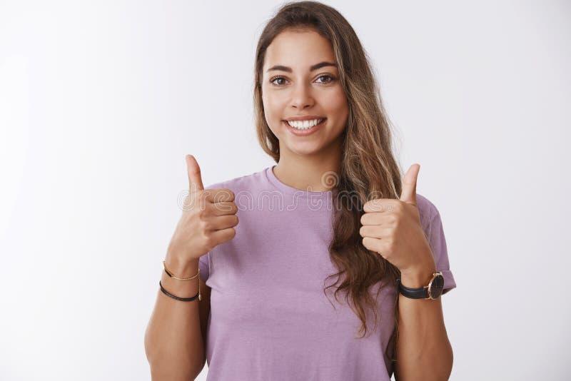 Il colpo della vita-su ha stimolato la giovane donna moderna affascinante uscente che mostra i pollici sull'approvazione piacevol immagini stock