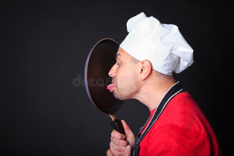 Il colpo dello studio del cuoco unico positivo lecca una padella immagine stock libera da diritti