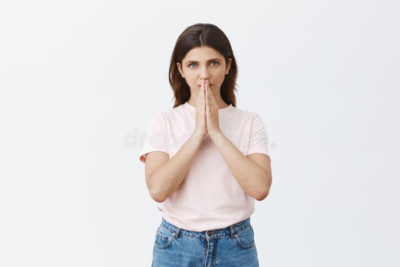 Il colpo dello studio della donna che ha fede in dio che si tiene per mano dentro prega vicino alla bocca ed a fissare serie e ca fotografia stock