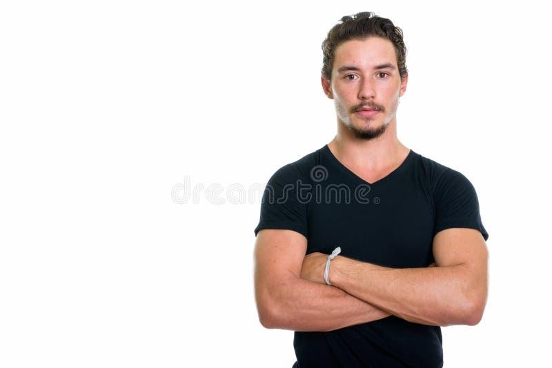 Il colpo dello studio di giovane uomo bello con le armi attraversate ha isolato il aga fotografie stock