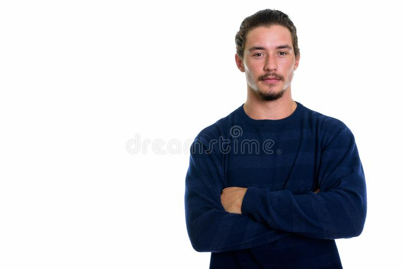 Il colpo dello studio di giovane uomo bello con le armi attraversate ha isolato il aga immagini stock