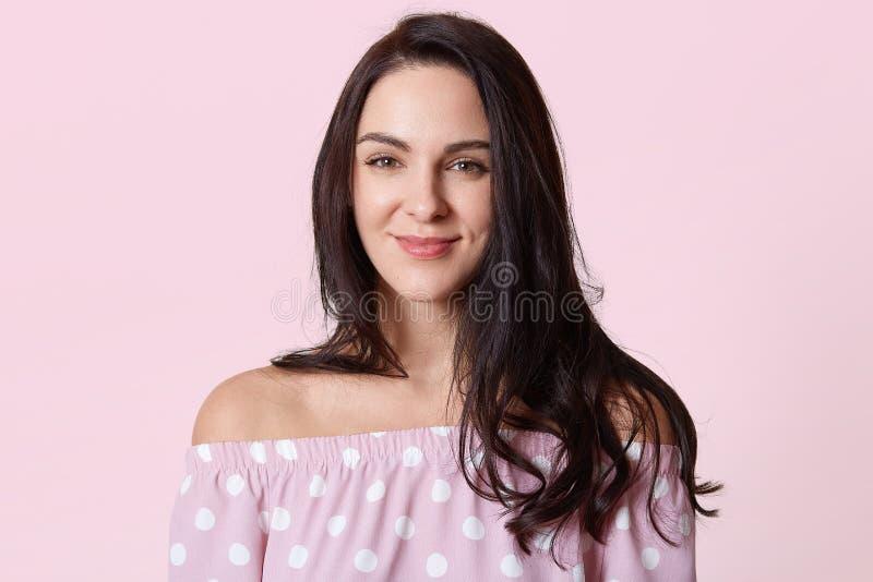 Il colpo di bella donna sorridente con pelle pulita, naturale compone, capelli castana lunghi che posano con le spalle nude, indo fotografia stock