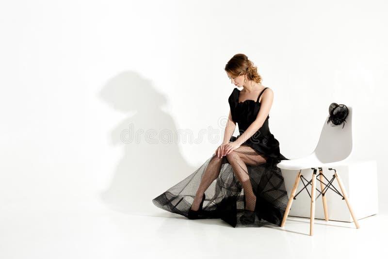 Il colpo di modo della donna triste elegante in vestito ed in velo neri si siede sulla sedia e sull'attesa sul fondo bianco fotografie stock libere da diritti