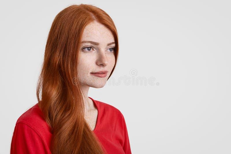 Il colpo obliquo di bella donna freckled dai capelli rossi con capelli lunghi, pensa a qualcosa, messo a fuoco nella distanza, ve fotografia stock libera da diritti