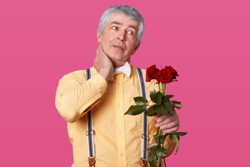 Il colpo orizzontale dell'uomo anziano dai capelli grigio in vestiti alla moda convenzionali, tiene la mano sul collo, ha dolore, fotografie stock
