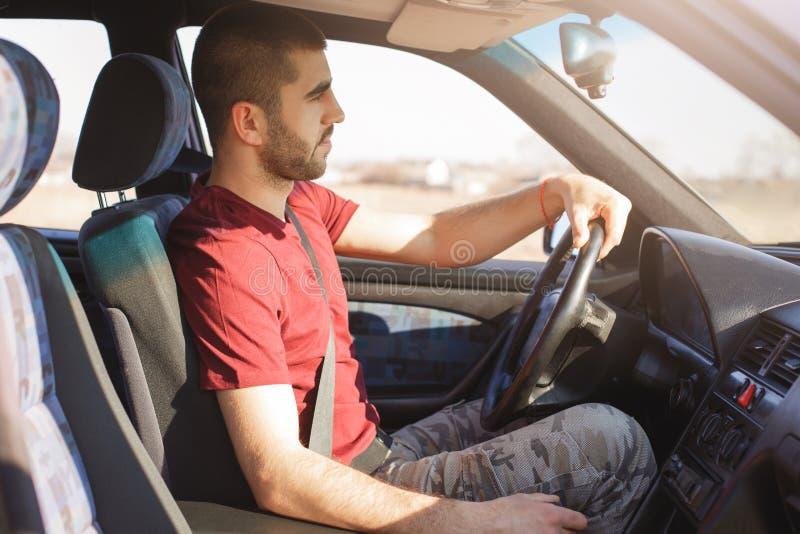 Il colpo orizzontale dell'uomo bello, indossa l'abbigliamento casual, conduce l'automobile e guarda direttamente nel parabrezza,  immagini stock