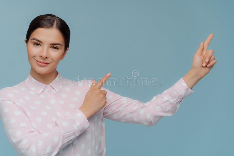 Il colpo orizzontale della donna adorabile nei punti alla moda dell'abbigliamento via nell'angolo sinistro vuoto, mostra lo spazi fotografia stock libera da diritti