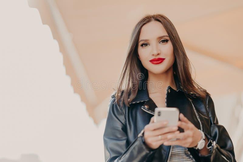 Il colpo orizzontale della femmina mora attraente con le labbra dipinte rosse, vestito in bomber nero, tiene il telefono cellular fotografia stock
