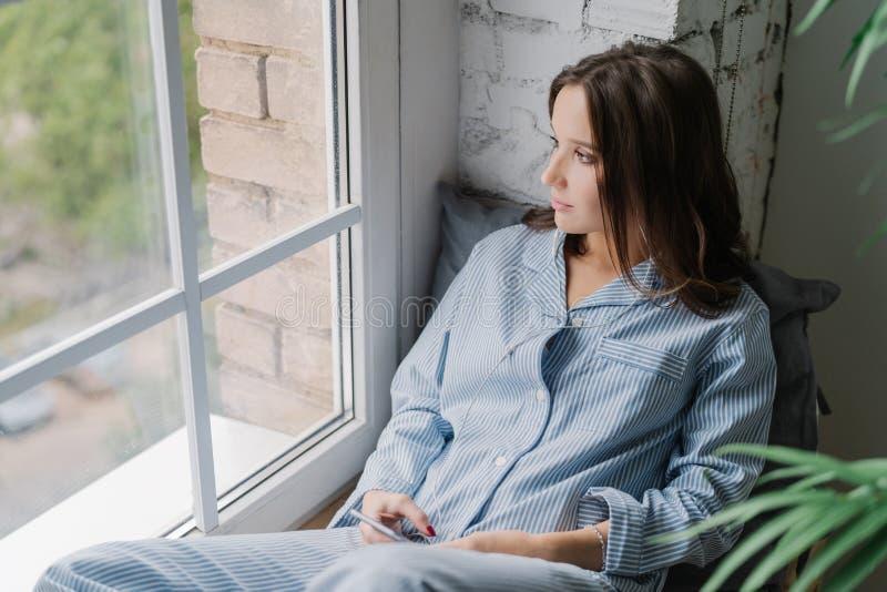 Il colpo orizzontale della giovane donna premurosa si siede sul davanzale, vestito in indumenti da letto casuali, usi Smart Phone immagine stock libera da diritti