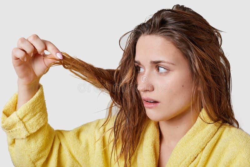 Il colpo orizzontale di bella donna dei capelli scuri esamina i suoi capelli nocivi bagnati, ha espressione facciale stressante,  immagini stock