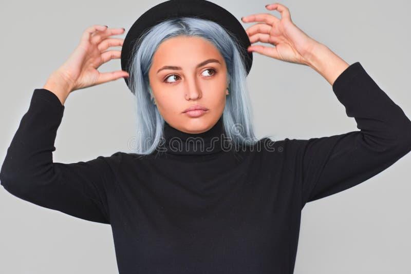 Il colpo schietto dello studio di bella giovane donna caucasica con capelli blu che esaminano un lato, porta il cappello, con l'e fotografia stock libera da diritti