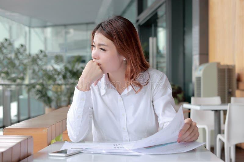 Il colpo schietto di giovane donna asiatica attraente di affari che pensa e che riposa un ` s osserva sullo scrittorio in ufficio immagini stock