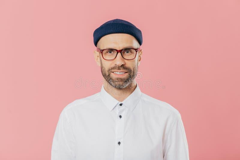 Il colpo in testa del giovane barbuto soddisfatto esamina con confidenza la macchina fotografica attraverso gli occhiali, porta l immagine stock