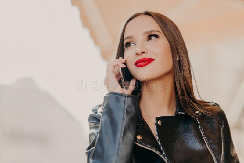 Il colpo in testa della donna vaga sembrante piacevole messa a fuoco da parte, ha conversazione telefonica, porta il cappotto di  fotografie stock