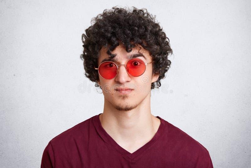 Il colpo in testa di giovane maschio barbuto alla moda fresco con capelli ricci, indossa i vetri rotondi rossi alla moda, aspetta fotografie stock libere da diritti