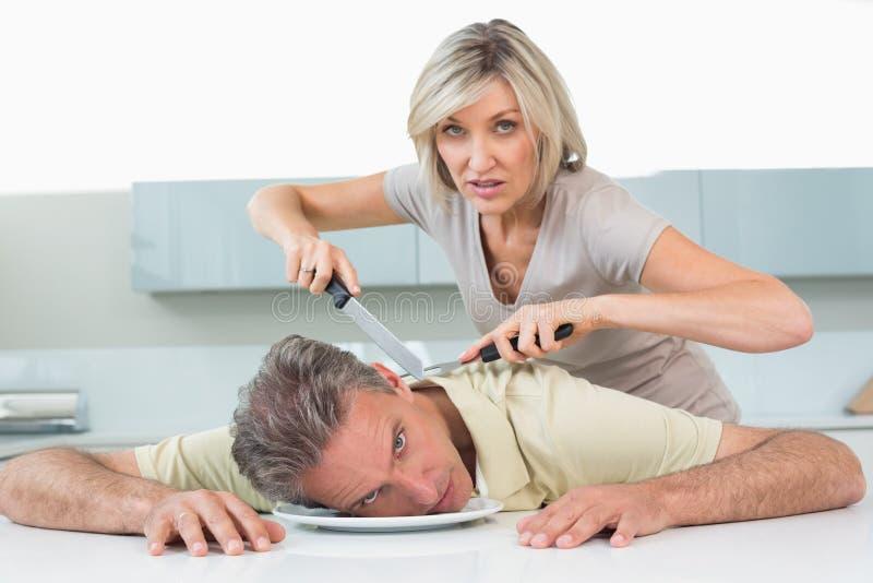 Il coltello arrabbiato della tenuta della donna equipaggia il collo in cucina immagine stock