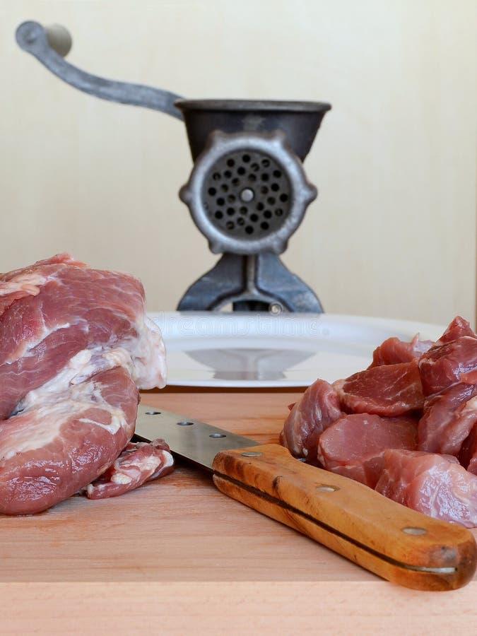 Il coltello e la carne per tritano su un tagliere di legno Dietro loro sono una tritacarne manuale d'annata e un piatto bianco su immagine stock libera da diritti