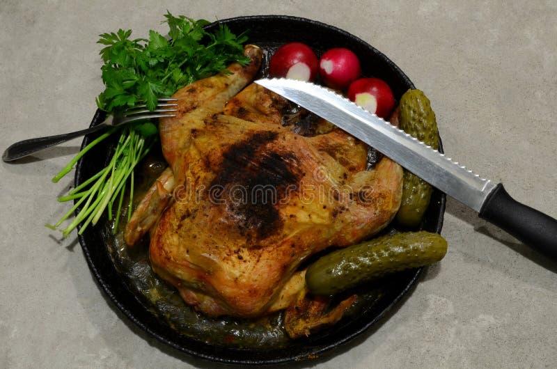 Il coltello e la forcella si trovano sopra un pollo fritto con i verdi fotografia stock