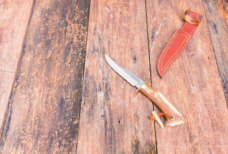 Il coltello per l'escursione in cuoio di marrone della guaina su fondo d'annata di legno con lo spazio della copia aggiunge il te fotografia stock libera da diritti