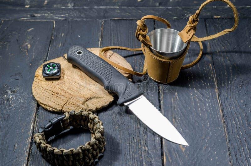 Il coltello più tagliente di un cacciatore Una bussola e una tazza del metallo fotografia stock libera da diritti