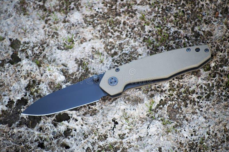 Il coltello piegante di viaggio ha reso di acciaio inossidabile con la lama nera fotografia stock
