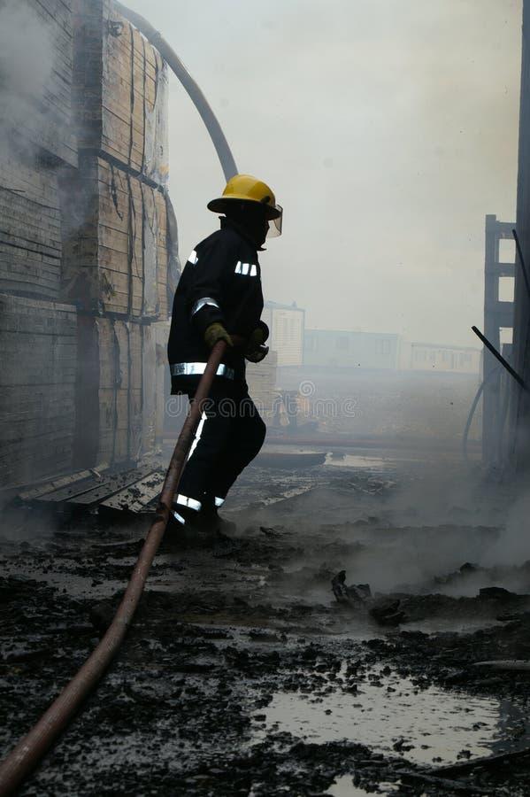 Il combattente di fuoco che entra in fumo ha riempito la costruzione fotografie stock