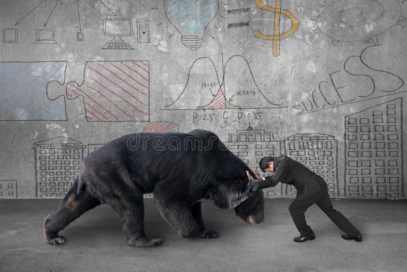 Il combattimento dell'uomo d'affari contro l'orso nero con il concetto di affari fa fotografia stock