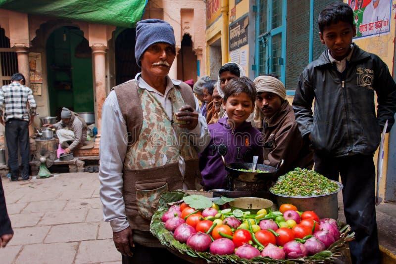 Il commerciante anziano dell'alimento della via presenta un piatto per tutti fotografie stock