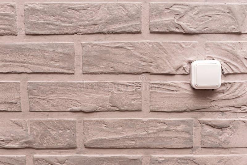 Il commutatore elettrico di plastica è situato sulla parete, decorata con gesso decorativo beige sotto forma di mattoni nell'inte immagini stock