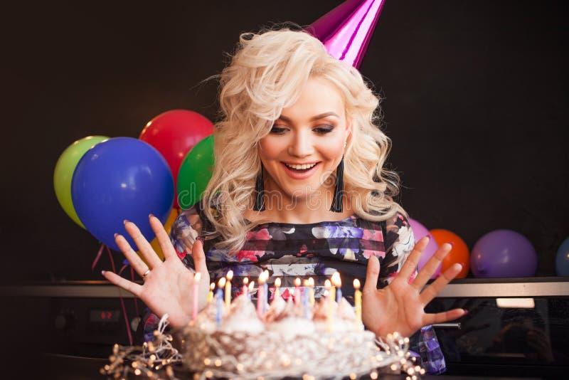 Il compleanno, una giovane donna spegne le candele sulla sua torta di compleanno immagini stock