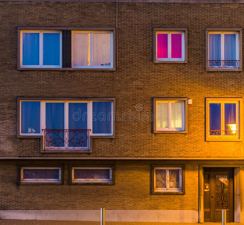 Il complesso di appartamenti si è acceso di notte, case belghe, sviluppando l'esterno con le finestre e l'entrata principale immagini stock libere da diritti