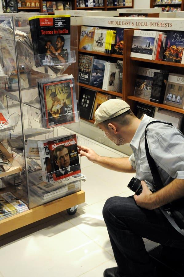 Il compratore elimina una rivista con presidente russo Dmitry Medvedev sulla copertura in una libreria nel Dubai fotografia stock libera da diritti