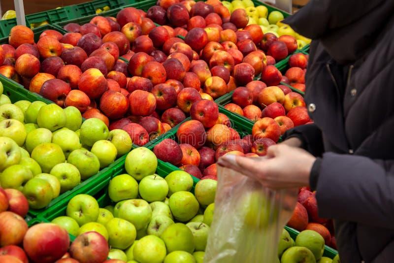 Il compratore sceglie le mele al contatore nel supermercato immagine stock