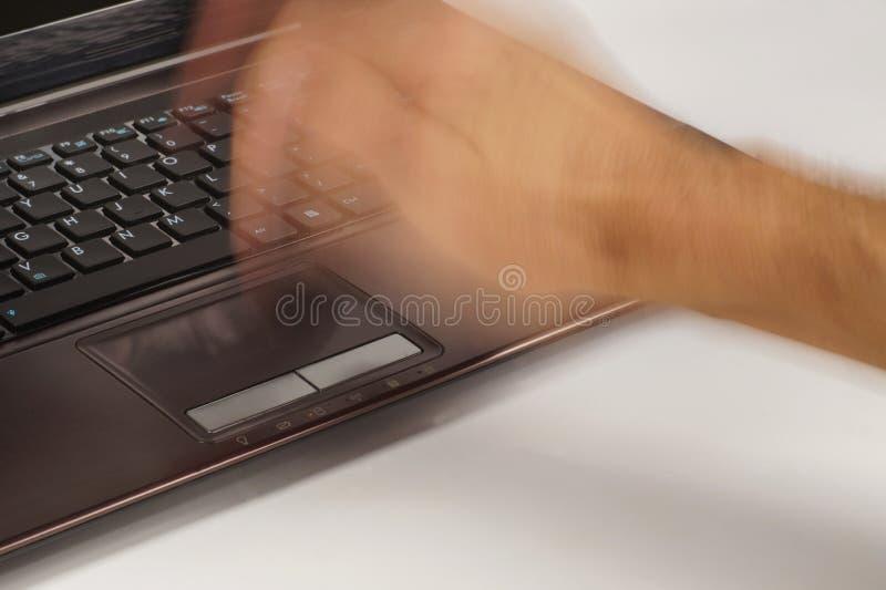 Il computer non vuole funzionare correttamente Una mano maschio che colpisce violentemente un touchpad del computer portatile immagini stock libere da diritti
