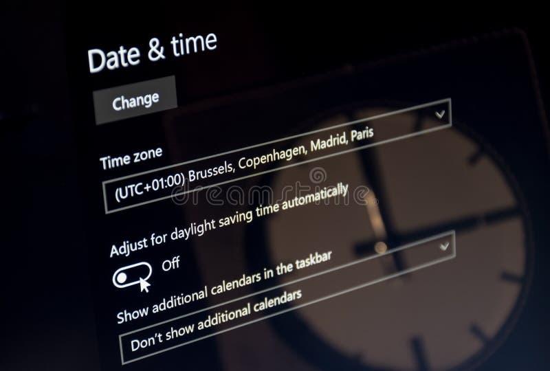 Il computer portatile che mostra il menu di tempo di risparmio del dayligt con un orologio ha riflesso sullo schermo UTC 01 fotografie stock libere da diritti